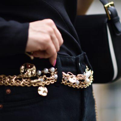 All Black Look mit asymmetrischem Oberteil und Kettengürtel