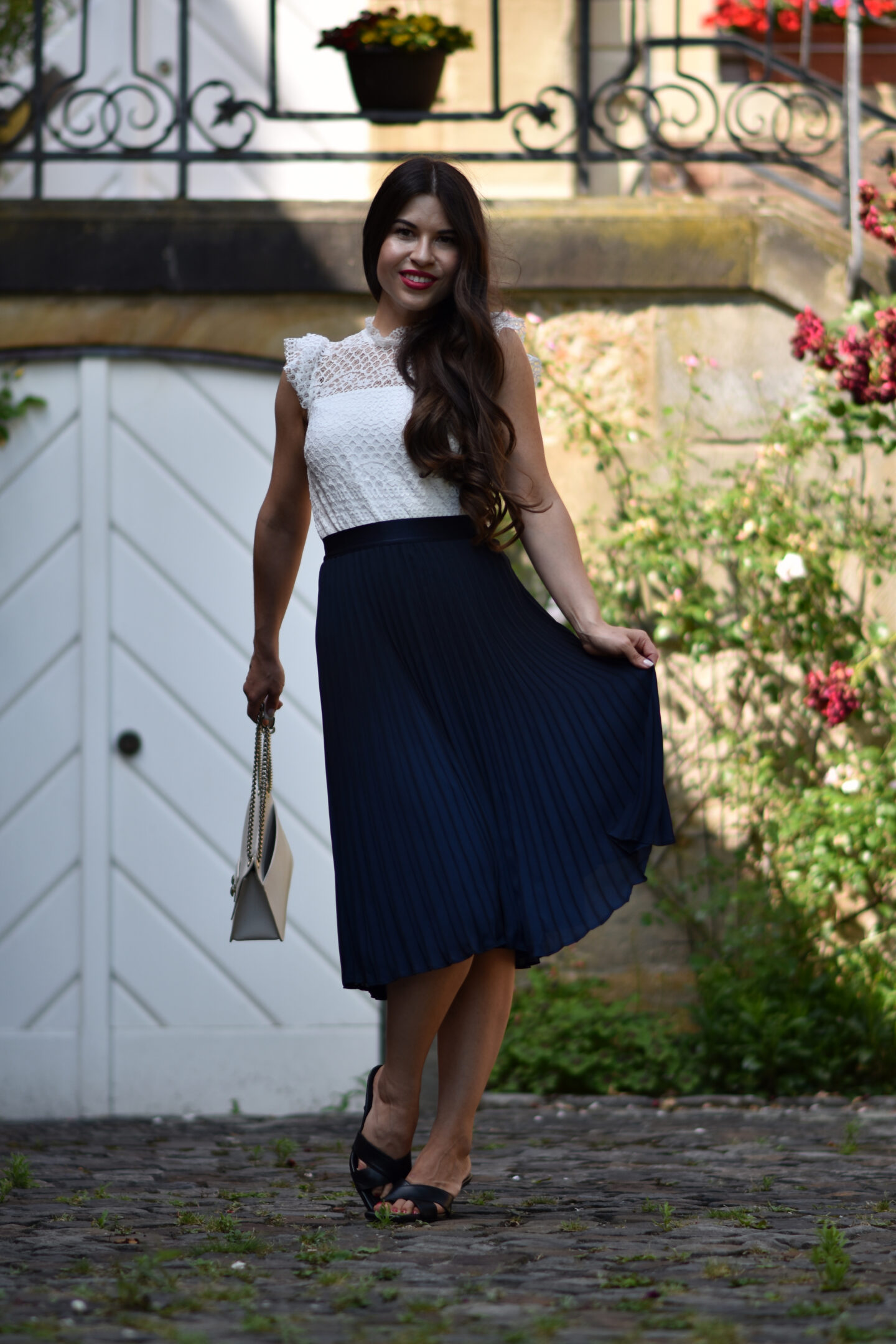 Elegant-femininer Look mit Plisseerock, Spitzentop & Sandalen
